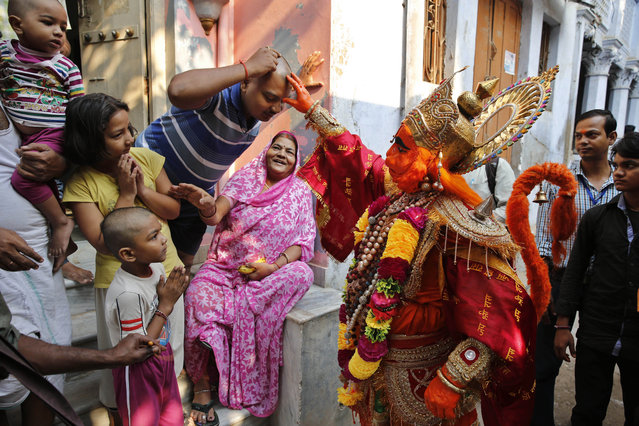 An Indian man dressed as monkey god Hanuman blesses bystanders as he participates in a procession on the eve of Diwali in Allahabad, India, Wednesday, October 22, 2014. The day before Diwali, the festival of lights, is a significant Hanuman worship day for Hindus. (Photo by Rajesh Kumar Singh/AP Photo)