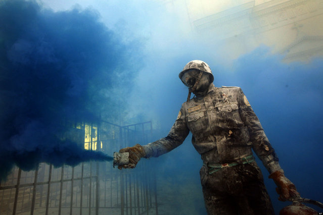 A reveler takes part in festival of Els Enfarinats, in the town of Ibi near Alicante, Spain, Friday, December 28, 2012. For 200 years the inhabitants of Ibi annually celebrate with a battle using flour, eggs and firecrackers, outside the city town hall. (Photo by Alberto Saiz/AP Photo)