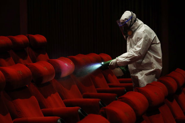 A worker of PVR cinemas, a multiplex cinema chain, sanitizes a hall during a press preview to show their preparedness with the COVID-19 pandemic in New Delhi, India, Friday, July 31, 2020. (Photo by Manish Swarup/AP Photo)