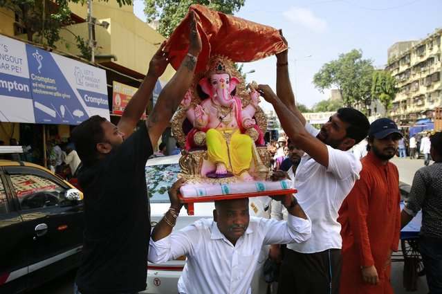 Indian devotees try to cover an idol of elephant-headed Hindu God Ganesha with cloth as they carry it for worship during Ganesh Chaturthi festival celebrations in Mumbai, India, Monday, September 5, 2016. The idols will be immersed in water bodies after worship at the end of the festival. (Photo by Rafiq Maqbool/AP Photo)