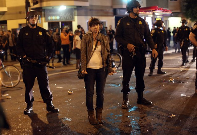 A woman stands as fans celebrate in the street in the Mission District after the San Francisco Giants defeated the Kansas City Royals in Game 7 of the World Series, in San Francisco, California October 29, 2014. (Photo by Robert Galbraith/Reuters)