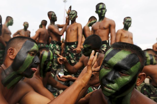 Indonesian soldiers help each other to apply camouflage paint before a rehearsal for the ceremony marking the 70th anniversary of Indonesia's military in Cilegon, Banten province, October 3, 2015. (Photo by Reuters/Beawiharta)