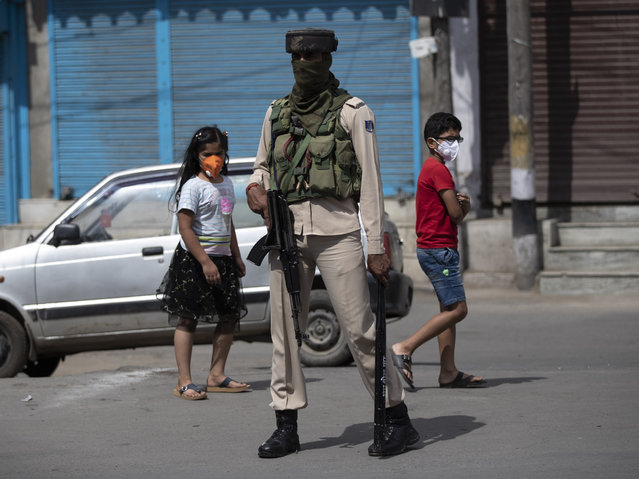 "Kashmiri children walk past a paramilitary soldier during curfew in Srinagar, Indian controlled Kashmir, Tuesday, August 4, 2020. Authorities clamped a curfew in many parts of Indian-controlled Kashmir on Tuesday, a day ahead of the first anniversary of India's controversial decision to revoke the disputed region's semi-autonomy. Shahid Iqbal Choudhary, a civil administrator, said the security lockdown was clamped in the region's main city of Srinagar in view of information about protests planned by anti-India groups to mark Aug. 5 as ""black day"". (Photo by Mukhtar Khan/AP Photo)"