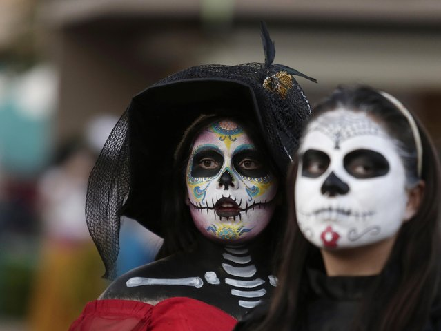 """Women with faces painted to look like the popular Mexican figure called """"Catrina"""" are seen in Zapopan October 30, 2014. According to participants, about 271 women gathered in an attempt at the Guinness World Record for the largest gathering of women dressed to look like """"Catrina"""", a character also known as """"The Elegant Death"""" and created by Guadalupe Posada in the early 1900s. (Photo by Alejandro Acosta/Reuters)"""