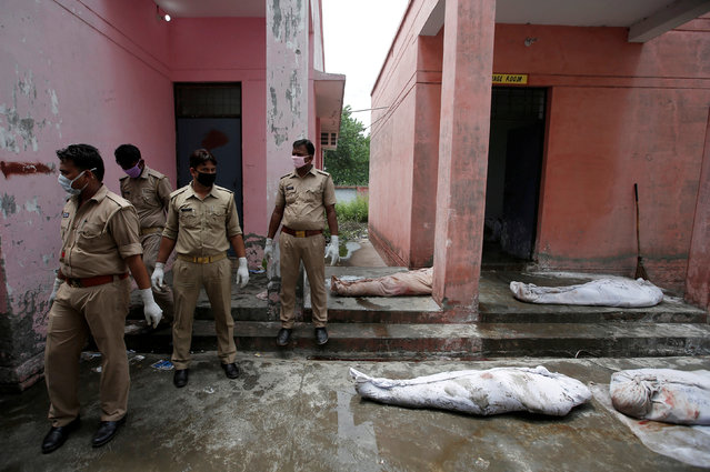 Police personnel stand next to the dead bodies of the victims of a passenger train accident, outside a mortuary in Muzaffarnagar, in Uttar Pradesh, India, August 20, 2017. (Photo by Adnan Abidi/Reuters)