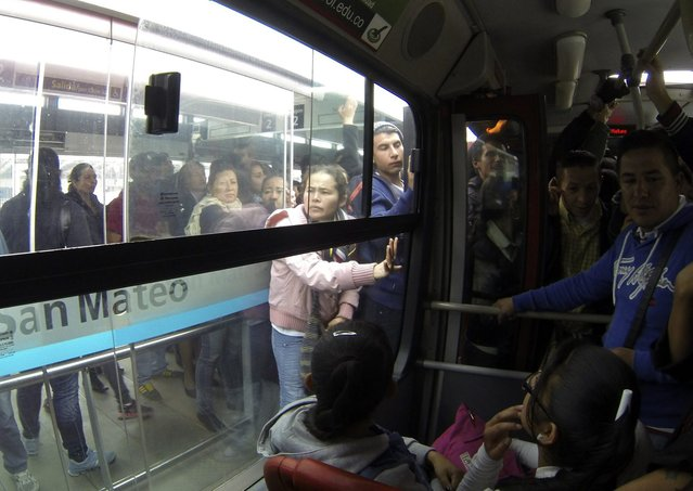 Passengers try to cram into a Transmilenio system bus during rush hour in Bogota, October 16, 2014. (Photo by John Vizcaino/Reuters)