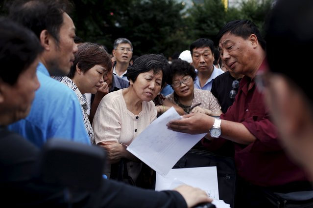 """Shen (4th L) listens to a man analysing a chart showing stock trends, at a """"street stock salon"""" in central Shanghai, China, July 4, 2015. Some are in it just for the money, others to help buy a meal. Then there are those who trade for fun or to spend time among friends. Millions of investors - pensioners, security guards, high-school students - dominate China's stock markets, conducting about 80 percent of all trades. (Photo by Aly Song/Reuters)"""