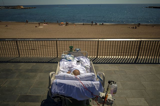 """Francisco España, 60, spends time in front of the beach near the """"Hospital del Mar"""" in Barcelona, Spain, Friday, September 4, 2020. A hospital in Barcelona is studying how short trips to the beach may help COVID-19 patients recover from long and traumatic intensive hospital care. The study is part of a program to """"humanize"""" ICUs. Since re-starting it in early June, the researchers have anecdotally noticed that even ten minutes in front of the blue sea waters can improve a patient's emotional attitude. (Photo by Emilio Morenatti/AP Photo)"""