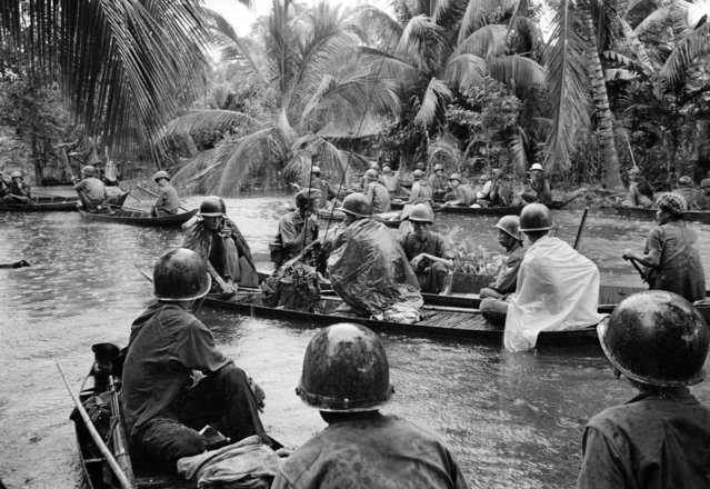 In a sudden monsoon rain, part of a company of about 130 South Vietnamese regional soldiers moves downriver in sampans during a dawn attack against a Viet Cong camp in the flooded Mekong Delta, about 13 miles northeast of Cantho, on January 10, 1966. A handful of guerrillas were reported killed or wounded. (Photo by Henri Huet/AP Photo)