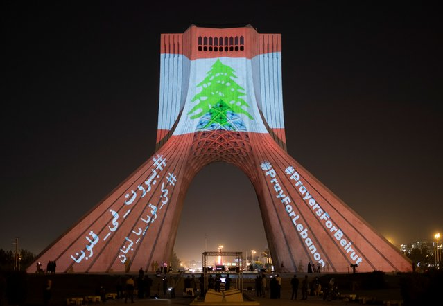 The video mapping is projected on the Azadi (Freedom) Monument in western Tehran, on August 5, 2020. A Lebanon flag projected on the Monument as a sign of unity between Iran and the Lebanon also a symbol of the Iranian people's sympathy for the victims of the recent explosions in Beirut. (Photo by Morteza Nikoubazl/NurPhoto via Getty Images)