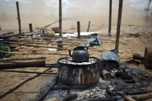 In this November 12, 2014 photo, a charred kettle sits on top of a scorched makeshift stove in an illegal gold mining camp, set ablaze by police as part of an operation to eradicate the illegal mining camps in the area known as La Pampa, in Peru's Madre de Dios region. (Photo by Rodrigo Abd/AP Photo)