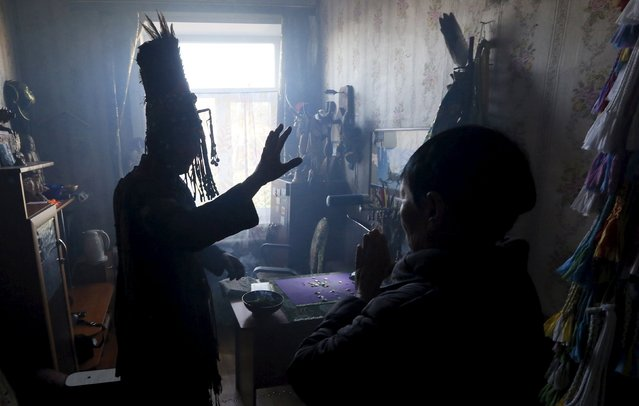 Yury Oorzhak (L), a shaman representing the so-called Adyg Eeren (Bear Spirit) society, conducts a session to clarify and predict the destiny of a customer, a local resident, at his residence in the town of Kyzyl, the administrative centre of Tuva region, Southern Siberia, Russia, October 7, 2015. (Photo by Ilya Naymushin/Reuters)
