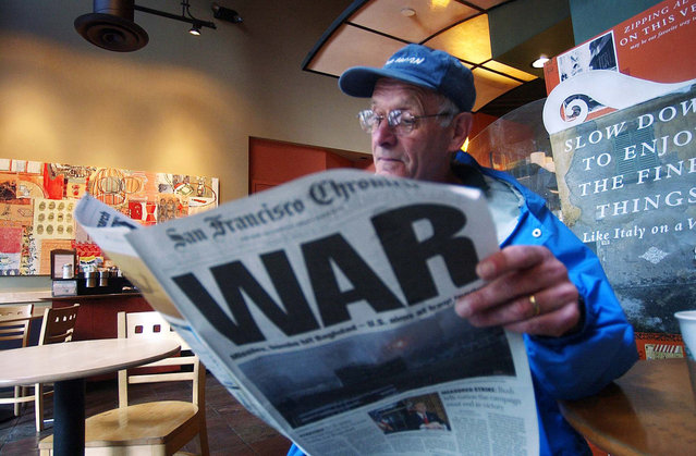Ray Jacques reads the San Francisco Chronicle's war special section inside a Starbucks coffee shop in San Francisco, in this March 20, 2003 photo. (Photo by Marcio Jose Sanchez/AP Photo/The Atlantic)