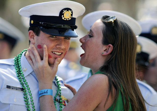 U.S Coast Guard Petty Officer 3rd Class Tanner Marshall is kissed by a woman during a St. Patrick's Day parade, Saturday, March, 16, 2013, in Savannah, Ga. St. (Photo by Stephen Morton/AP Photo)