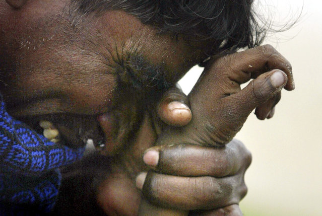 An Indian man cries as he holds the hand of his eight-year-old son who was killed in a tsunami in Cuddalore, south of the Indian city of Madras, in this December 27, 2004 file photo. (Photo by Arko Datta/Reuters)