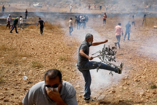 Palestinian demonstrators react to tear gas fired by Israeli forces during a protest against Jewish settlements, in Beit Dajan near Nablus in the Israeli-occupied West Bank on October 9, 2020. (Photo by Raneen Sawafta/Reuters)