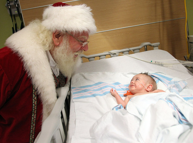 A Macy's Santa Claus visits with 8-month-old Brystal Logsdon of Grayson, Ky., on Tuesday, December 2, 2014, at Hoops Family Children's Hospital at Cabell Huntington Hospital in Huntington, W.Va. (Photo by Lori Wolfe/AP Photo/The Herald-Dispatch)