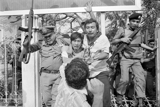 In this October 6, 1976, file photo, a right-wing student, center foreground, draws his arm back to strike a captured and wounded leftist student being taken by police to an ambulance in during a student massacre in Bangkok, Thailand. This year's anti-government protests are seeking new elections, a more democratic constitution and an end to intimidation of political activists. Their speeches have repeatedly highlighted the 1976 tragedy, piquing the interest of the current generation in what their forebears faced. (Photo by Neal Ulevich/AP Photo/File)