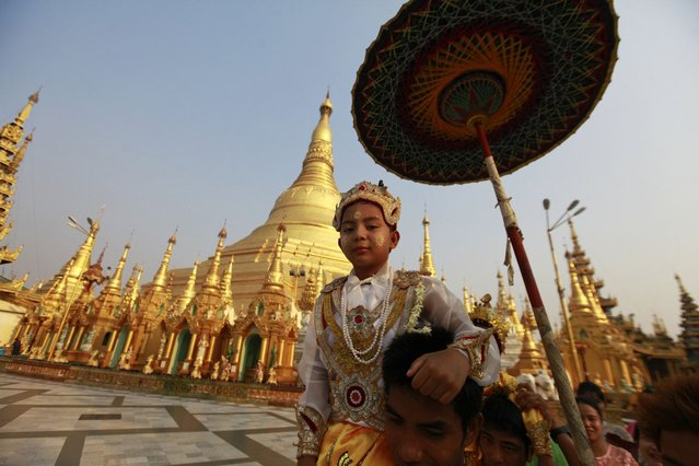 """A boy rides on the shoulders his family members as they proceed through the compounds of the Shwedagon Pagoda during their """"Shin Phu"""", a ceremony to initiate novice monks, in Yangon, Myanmar, on April 3, 2013. (Photo by Soe Zeya Tun/Reuters)"""