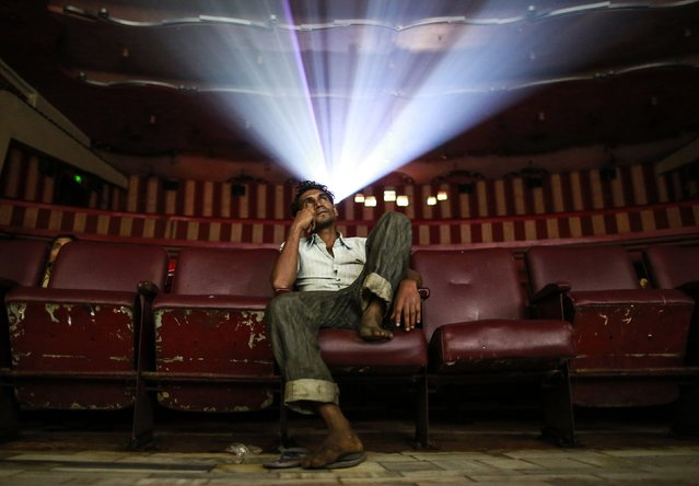 "A cinema goer watches Bollywood movie ""Dilwale Dulhania Le Jayenge"" (The Big Hearted Will Take the Bride), starring actor Shah Rukh Khan, inside Maratha Mandir theatre in Mumbai December 11, 2014. (Photo by Danish Siddiqui/Reuters)"