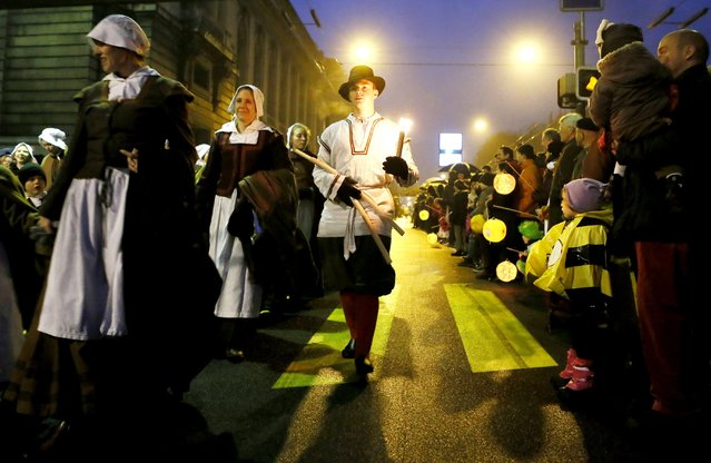 Members of the Compagnie 1602 take part in a procession in Geneva December 14, 2014. (Photo by Pierre Albouy/Reuters)