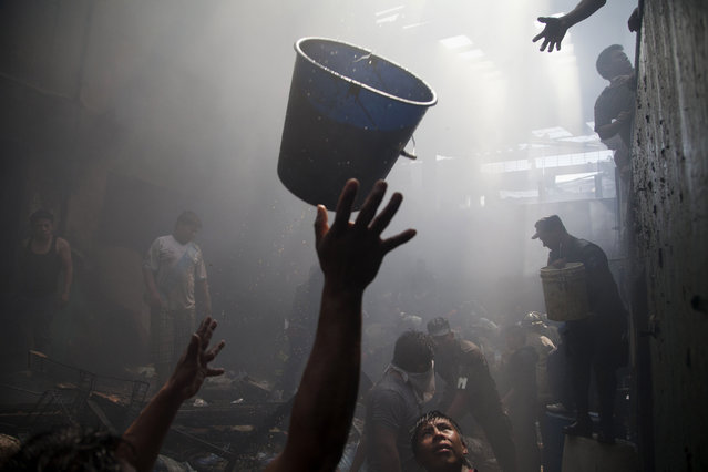 In this March 25, 2014 file photo, people reach out to receive a bucketful of water as vendors, police and firemen work together to put out a fire at La Terminal, the largest and most important market in Guatemala City. Firefighters struggled to manage the fire that destroyed hundreds of shops due to the lack of water hydrants in the area, located south of the historic city center. (Photo by Moises Castillo/AP Photo)