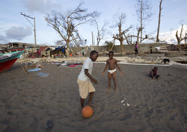 Boys play soccer on the ground of a destroyed house after the Hurricane Matthew in Dame-Marie, Haiti on Monday, October 10, 2016. (Photo by Dieu Nalio Chery/AP Photo)