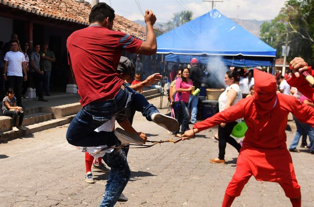 "Faithfuls try to avoid being lashed by ""talciguines"" – characters of the local folklore- during the celebration of an ancient local tradition that marks the start of Holy Week, in Texistepeque, some 80 km west of San Salvador, on March 26, 2018 Talciguines are devils who lash Catholic faithfuls to cleanse their sins. (Photo by Marvin Recinos/AFP Photo)"