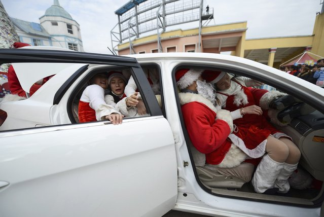 Staff dressed as Santa Claus try to squeeze into a car at a theme park in Changsha, December 18, 2014. Nineteen staff managed to get inside the car during the game. (Photo by Reuters/China Daily)
