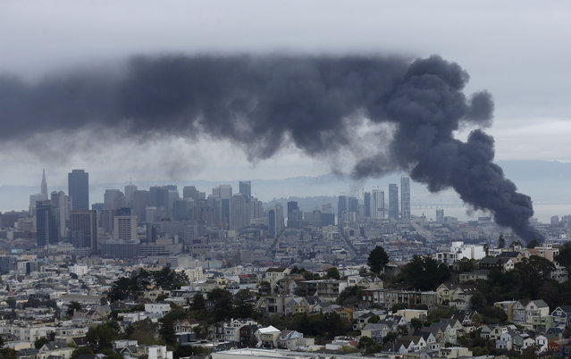 Smoke rises over the San Francisco skyline as a fire burns in the Mission District in San Francisco, Sunday, November 8, 2015. (Photo by Jeff Chiu/AP Photo)