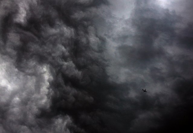 "A Qantas Airways Boeing 737-800 plane flies near storm clouds above Sydney December 7, 2014. The Australian Bureau of Meteorology issued a severe thunderstorm warning for Sydney and surrounding areas late this afternoon, stating that the storms were ""likely to produce large hailstones, damaging winds and heavy rainfall that may lead to flash flooding in the warning area"". (Photo by David Gray/Reuters)"