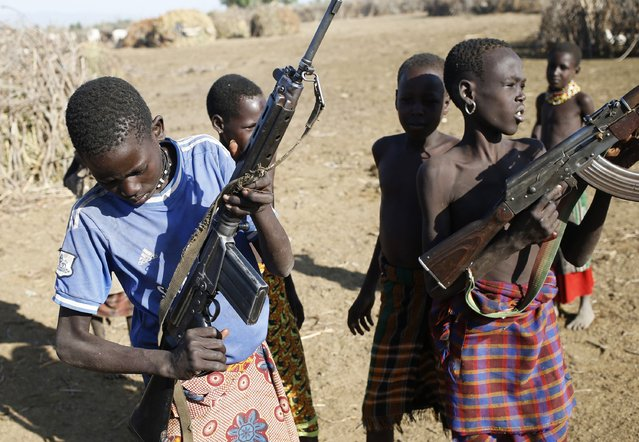Turkana boys play with rifles in a village inside the Turkana region of the Ilemi Triangle, northwest Kenya December 21, 2014. (Photo by Goran Tomasevic/Reuters)