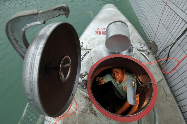Zhang Wuyi sits in his double-seater submarine during a test operation at an artificial pool near a shipyard in Wuhan, Hubei province May 7, 2012. Zhang, a 37-year-old local farmer, who is interested in scientific inventions, has made six miniature submarines with several fellow engineers, one of which was sold to a businessman in Dalian at a price of 100,000 yuan ($15,855) last October. The submarines, mainly designed for harvesting aquatic products, such as sea cucumber, have a diving depth of 20-30 metres, and can travel for 10 hours, local media reported. Picture taken May 7, 2012. (Photo by Reuters/Stringer)