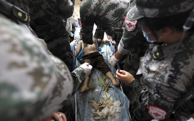 An injured child is treated by medical personnel after a landslide hit Lushan county, where a strong quake struck last month killing 196 people, in Ya'an, Sichuan province May 9, 2013. At least two people were killed and seven injured in the landslide on Thursday, according to Xinhua News Agency. (Photo by Reuters/China Daily)