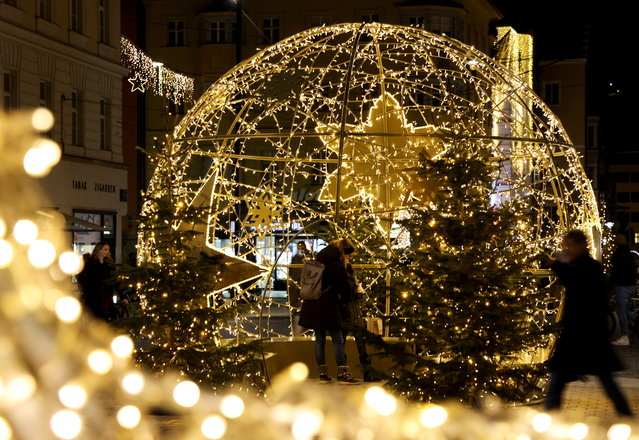 People pass by the Christmas illuminations, as the outbreak of the coronavirus disease (COVID-19) continues, in Innsbruck, Austria on December 15, 2020. (Photo by Leonhard Foeger/Reuters)