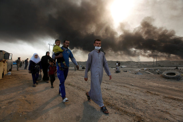 Civilians return to their village after it was liberated from Islamic State militants, south of Mosul in Qayyara, Iraq, October 22, 2016. The fumes in the background are from oil wells that were set ablaze by Islamic State militants. (Photo by Alaa Al-Marjani/Reuters)