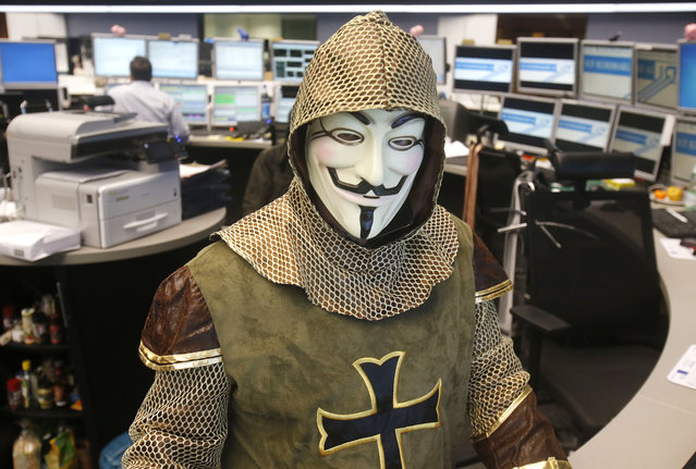Germany: A trader wears a Guy Fawkes mask and costume on the occasion of carnival at the stock market in Frankfurt, Germany, Tuesday, March 4, 2014. (Photo by Michael Probst/AP Photo)