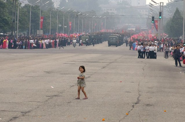 A girl walks into the street after the parade passes, September 2011. (Eric Testroete)