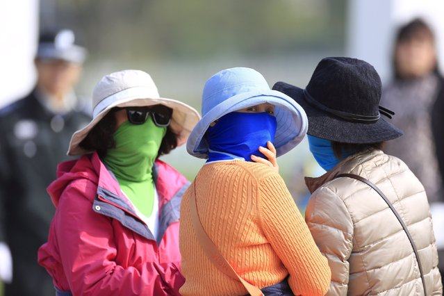 Women wear face masks on the fourth green during the third round of the BMW Masters 2015 golf tournament at Lake Malaren Golf Club in Shanghai, China, November 14, 2015. (Photo by Aly Song/Reuters)