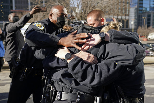 Nashville Police Chief John Drake, left, joins a group of police officers as they embrace after speaking at a news conference Sunday, December 27, 2020, in Nashville, Tenn. The officers are part of a group of officers credited with evacuating people before an explosion took place in downtown Nashville early Christmas morning. (Photo by Mark Humphrey/AP Photo)