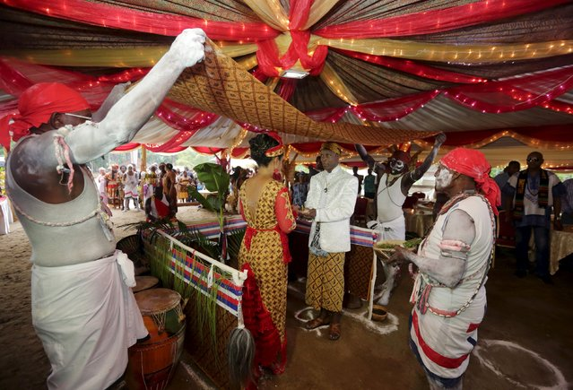 Winti spiritual leader Ramon Mac-Nack (center R) and his bride Melissa Karwafodi stand under a ceremonial cloth as they are wedded in the first Winti marriage ever to be held in public, as a Maroon priest (R) presides in district Para, Suriname, November 16, 2015. (Photo by Ranu Abhelakh/Reuters)