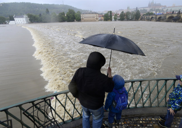 A family watches the swollen Vltava river in the center of Prague, Czech Republic, Sunday, June 2, 2013. Heavy rainfalls cause flooding along rivers and lakes in Germany, Austria, Switzerland and the Czech Republic. (Photo by Roman Vondrous/AP Photo/CTK)