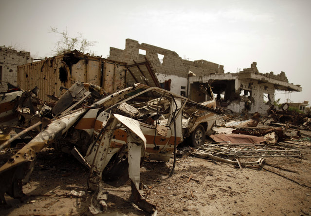 Vehicles and buildings destroyed during recent fighting between the army and al Qaeda-linked militants are seen on a road leading to the southern Yemeni city of Zinjibar June 14, 2012. (Photo by Khaled Abdullah/Reuters)