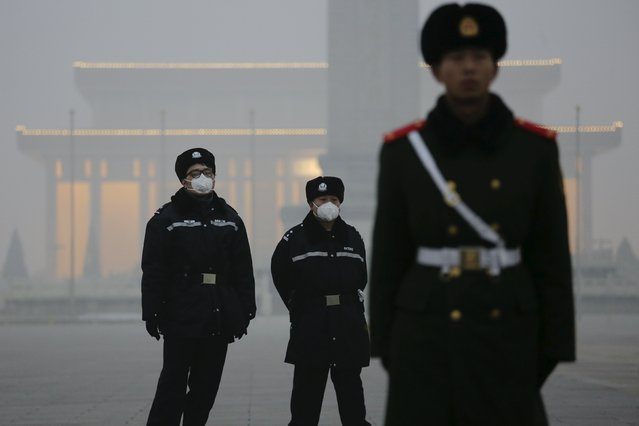 Policemen wear protective masks behind a paramilitary soldier at the Tiananmen Square on an extremely polluted day as hazardous, choking smog continues to blanket Beijing, China December 1, 2015. (Photo by Damir Sagolj/Reuters)