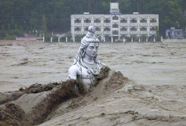 A submerged statue of the Hindu Lord Shiva stands amid the flooded waters of river Ganges at Rishikesh in the Himalayan state of Uttarakhand June 17, 2013. Early monsoon rains have swollen the Ganges, India's longest river, swept away houses, killed at least 60 people and left tens of thousands stranded, officials said on June 18, 2013. (Photo by Reuters/Stringer)