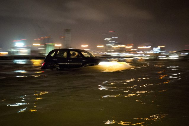 A driver manages to save his car from a flooded parking lot at the Fish Market in Hamburg, Germany, 11 January 2015. Strong winds caused several storm surges in Northern Germany. (Photo by Daniel Bockwoldt/EPA)