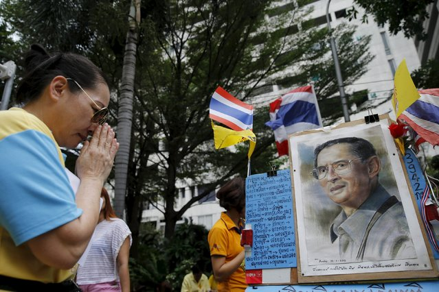 A supporter of Thai King Bhumibol Adulyadej prays outside Siriraj hospital, where a group gathered to mark his 88th birthday, in Bangkok December 5, 2015. Thais marked the birthday of King Bhumibol Adulyadej, the world's longest-reigning monarch, early on Saturday, by giving alms at temples around the country. Celebrations in Thailand, where the monarch's birthday is also national Father's Day, come amid a widening police investigation into a group of people charged with insulting the monarchy. The king has spent the past few months at the hospital being treated for hydrocephalus. (Photo by Jorge Silva/Reuters)