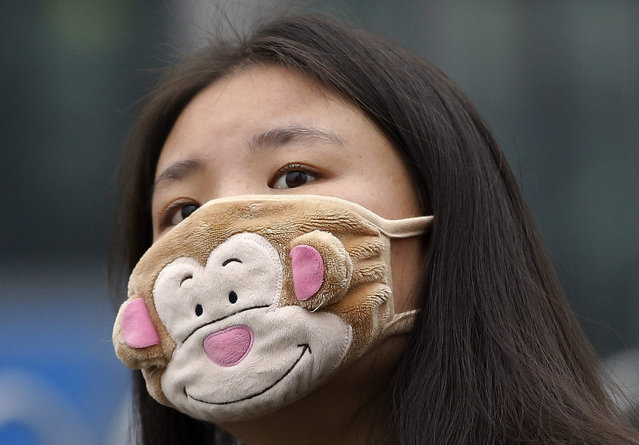 In this December 8, 2015 photo, a woman wears a mask to protect herself from pollutants on a heavily polluted day in Beijing. Episodes of nauseating smog lasting several days has become part of wintertime in Beijing. (Photo by Andy Wong/AP Photo)