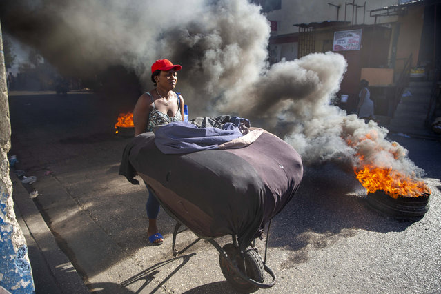 A woman pushes her merchandise away from tires set fire by protesters during a countrywide strike demanding the resignation of Haitian President Jovenel Moise in Port-au-Prince, Haiti, Monday, February 1, 2021. Opposition leaders are pushing for Moïse to step down on Feb. 7 while Moïse has said his term ends in February 2022. (Photo by Dieu Nalio Chery/AP Photo)