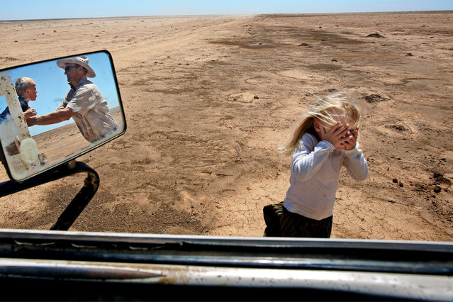A farmer and his children play in a water-starved area where his livestock once grazed in Australia, 2008. (Photo by Amy Toensing/National Geographic)